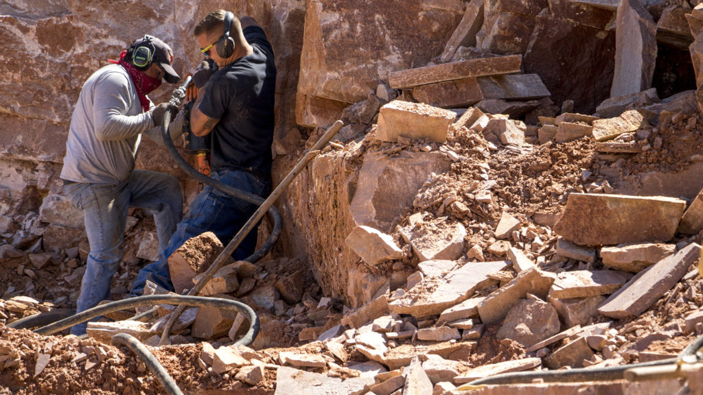 Lupe Lopez (left) and Jon Hickman drill into the side of a mountain at Lyons Sandstone's quarry, Sept. 10, 2018. (Kevin J. Beaty/Denverite)