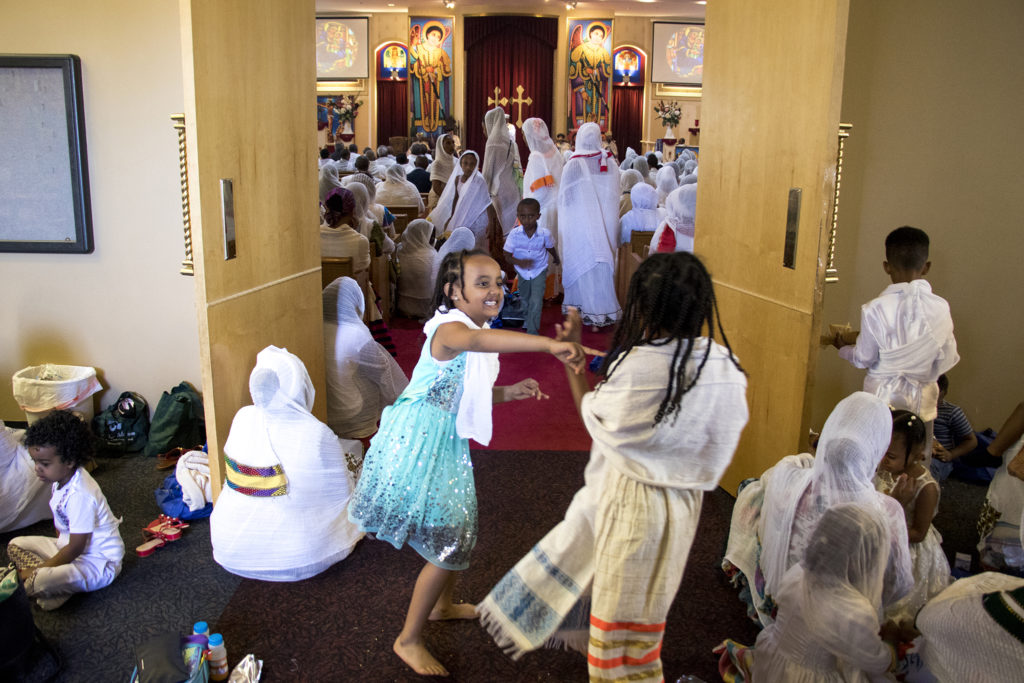 Kids play outside of the sanctuary during Ethiopian New Year services at St. Mary Ethiopan Orthodox Church in Aurora, Sept. 9, 2018. (Kevin J. Beaty/Denverite)