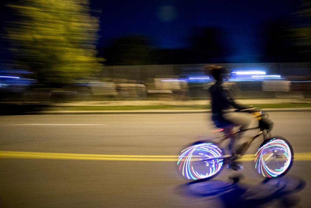 A woman rides an illuminated bike after Grandoozy at Overland Golf Course, Sept. 14, 2018. (Kevin J. Beaty/Denverite)