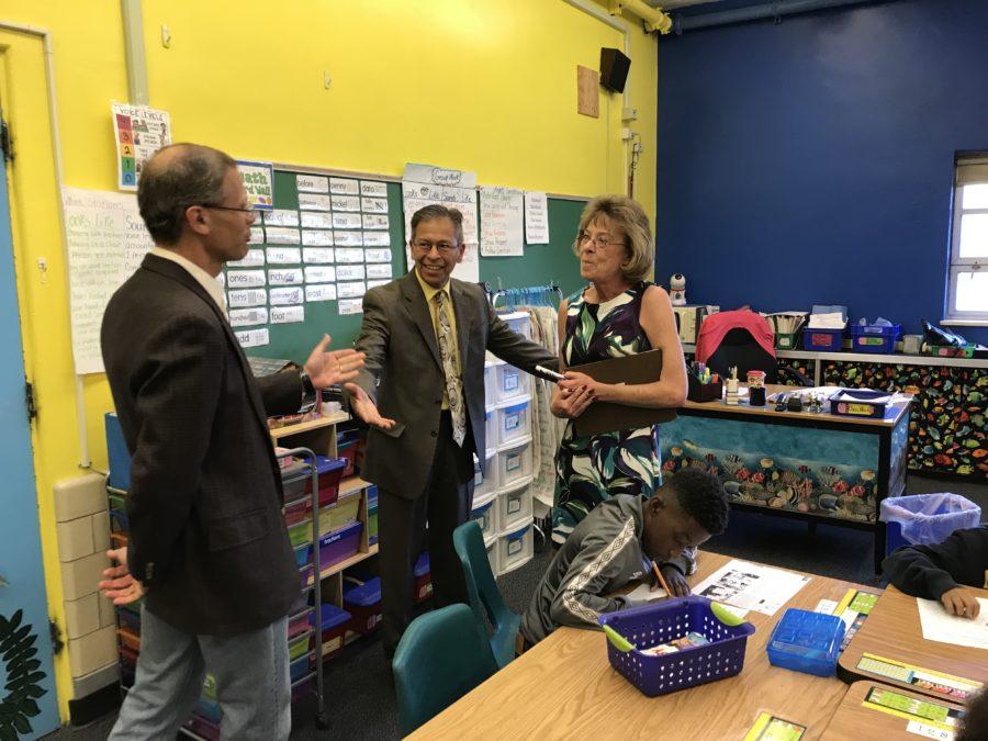 Denver Superintendent Tom Boasberg tells Stedman Elementary teacher Dawn Romero that her former principal, Ron Cabrera, center, is the new interim superintendent. (Melanie Asmar/Chalkbeat)