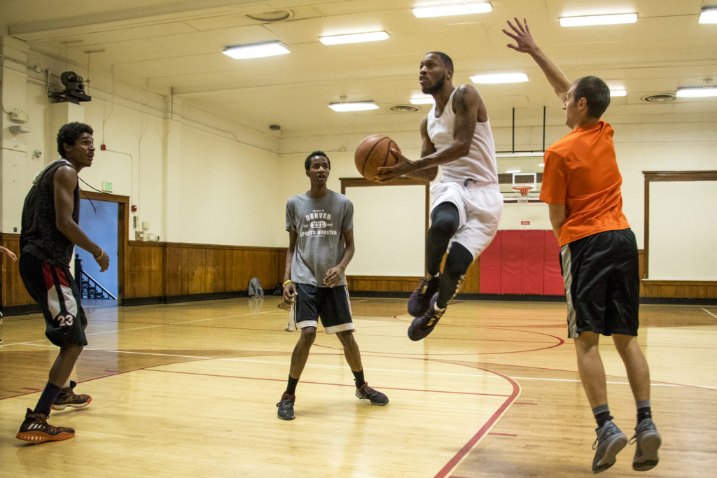 DJ Robinson leaps in the air during a pick-up basketball game at the Twentieth Street Recreation Center downtown, Oct. 16, 2018. (Kevin J. Beaty/Denverite)