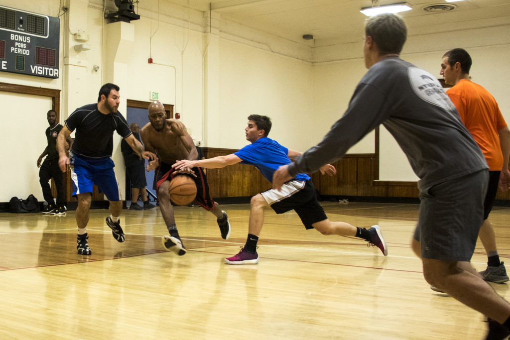 Bryce Hentges (in blue) reaches for the ball during a pick-up basketball game at the Twentieth Street Recreation Center downtown, Oct. 16, 2018. (Kevin J. Beaty/Denverite)