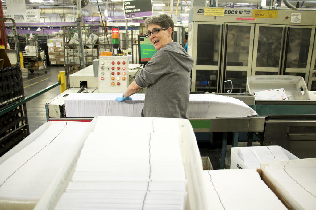 Kim Padilla feeds ballots into a sorting maching inside the U.S. Postal Service's massive sorting and shipping facility in Stapleton, Oct. 16, 2018. (Kevin J. Beaty/Denverite)