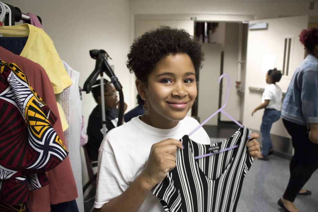 Ryomi (11) poses with one of her outfits before Curls on the Block's second-annual Miss Curly Pageant. Collegiate Prep Academy, Montbello, Oct. 21, 2018. (Kevin J. Beaty/Denverite)