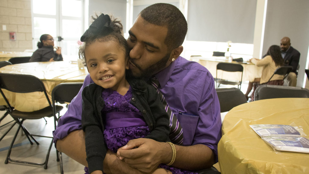 Ashlyn (2) sits on her father, Tony Bonds', lap before A Father Daughter Occasion begins at the Dahlia Campus for Health and Well-Being in Northeast Park Hill, Oct. 27, 2018. (Kevin J. Beaty/Denverite)