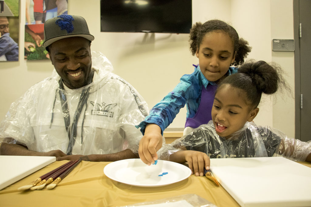 Rory (7) delivers paint to Kealani (6) and her dad, DeShawn Mayberry, duirng A Father Daughter Occasion at the Dahlia Campus for Health and Well-Being in Northeast Park Hill, Oct. 27, 2018. (Kevin J. Beaty/Denverite)