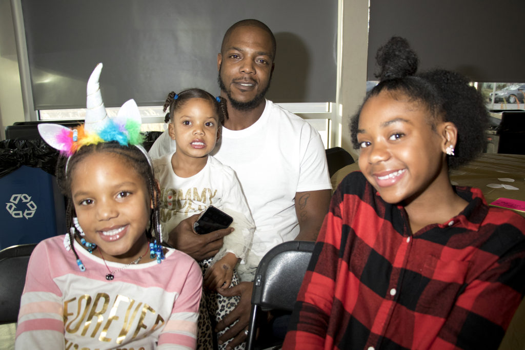 Eric Wedgeworth poses for a portrait with his daughters Aryss (6, left to right), Avynn (4) and Aniya (13). A Father Daughter Occasion at the Dahlia Campus for Health and Well-Being in Northeast Park Hill, Oct. 27, 2018. (Kevin J. Beaty/Denverite)