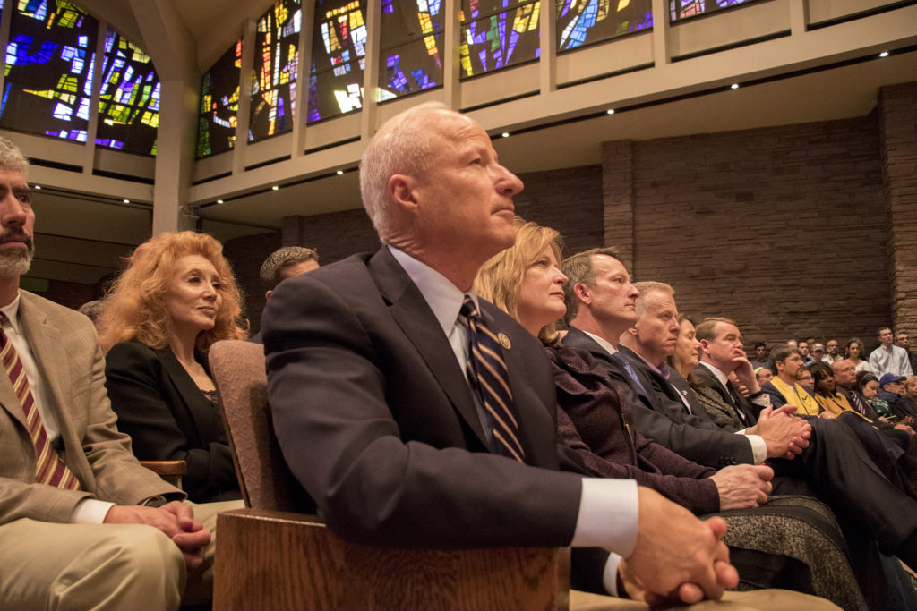 Congressman Mike Coffman sits at the end of a long line of politicians. A vigil at Temple Emanuel in Denver's Hilltop neighborhood for the victims in a mass shooting at a Pittsburgh synagogue, Oct. 28, 2018. (Kevin J. Beaty/Denverite)