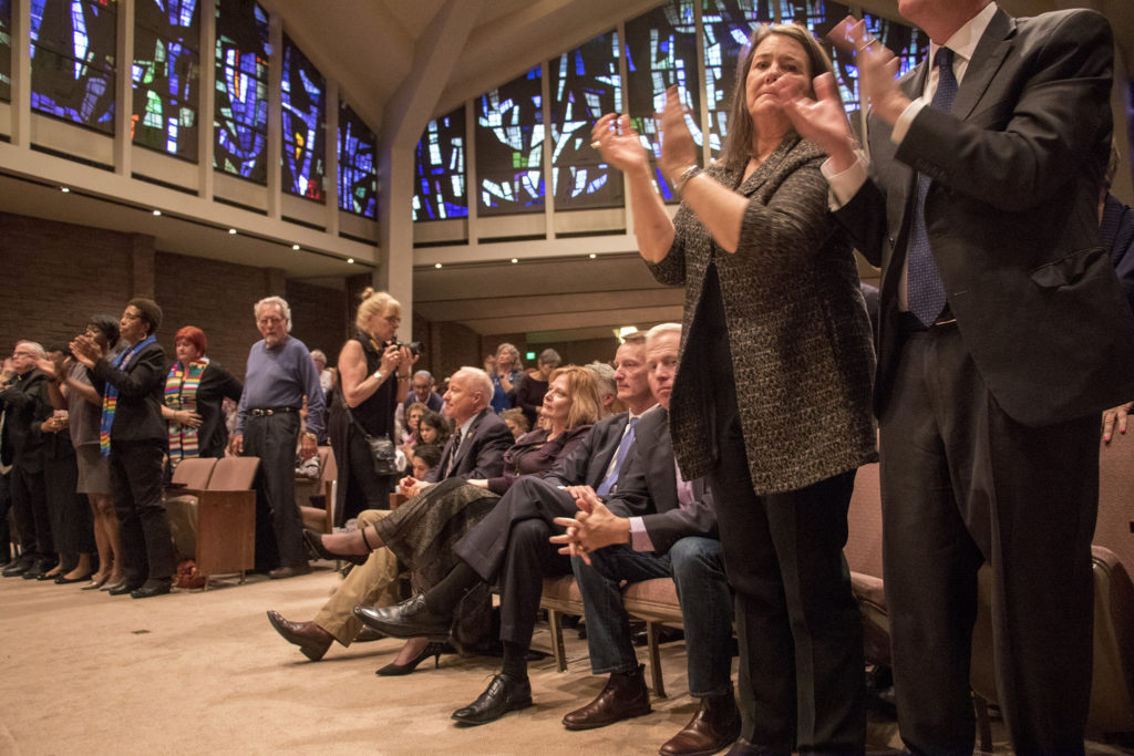 Colorado Republicans remain seated as many in the room gives a standing ovation after Colorado Sikhs Director Dilpreet Jammu slams Americans' support of the Second Amendment. A vigil at Temple Emanuel in Denver's Hilltop neighborhood for the victims in a mass shooting at a Pittsburgh synagogue, Oct. 28, 2018. (Kevin J. Beaty/Denverite)