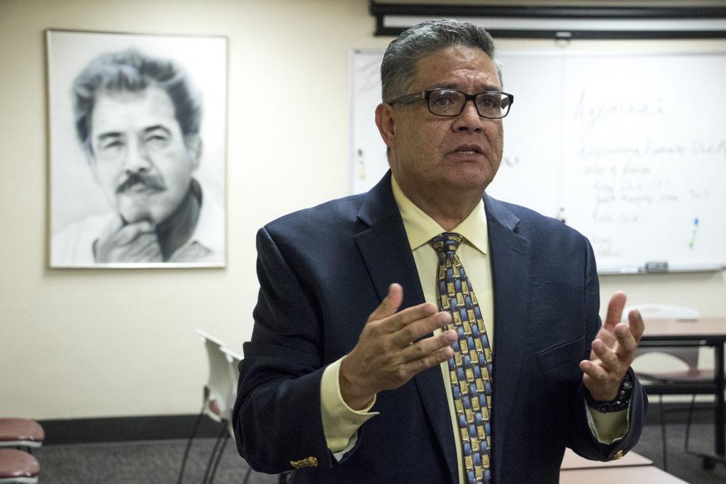 Servicios de la Raza executive director Rudy Gonzales welcomes a delegation of Colorado Democrat candidates. That's a picture of his father, Corky Gonzales, behind him. Oct. 30, 2018. (Kevin J. Beaty/Denverite)