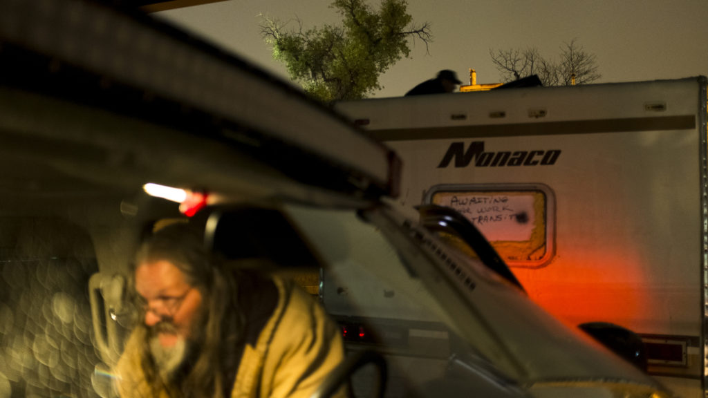 John Jenkins grabs supplies for people staying in an RV beneath a bridge as part of the Salvation Army's nightly search and rescue service, Oct. 30, 2018. (Kevin J. Beaty/Denverite)