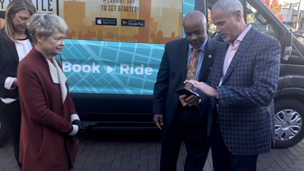 Chariot CEO Dan Grossman shows Mayor Michael Hancock how the Chariot app works as City Councilwoman Mary Beth Susman looks on. (David Sachs/Denverite)