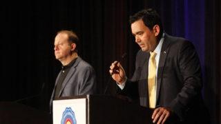 Republican gubernatorial candidate Walker Stapleton leans into a mic next to Jared Polis, the Democratic gubernatorial candidate, during a business forum on Friday, Oct. 5, 2018, in Denver. (Esteban L. Hernandez/Denverite)