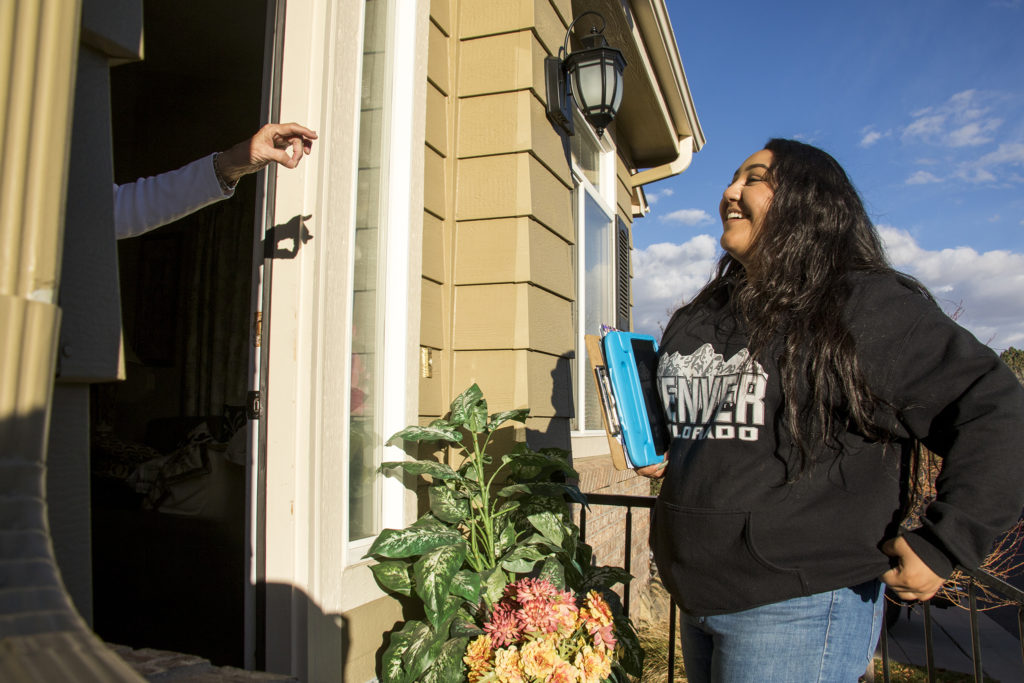 Sashikala Rubio-Rodriguez speaks with Louise M. Hall as she canvasses for the Coloado Immigrants Rights Coalition in Thornton, Nov. 1, 2018. (Kevin J. Beaty/Denverite)