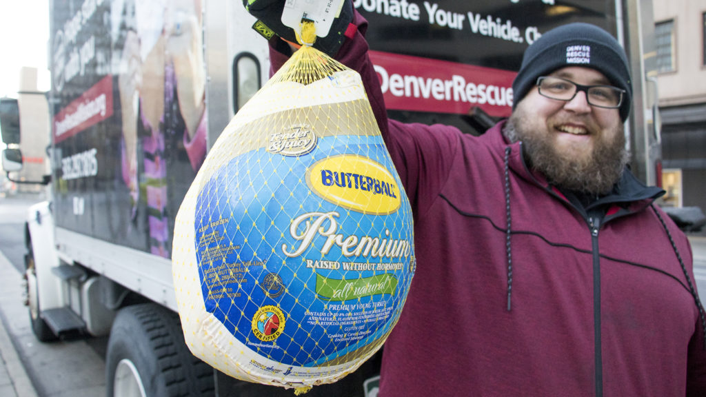 Jeremy Stubbs, food distribution coordinator for the Denver Rescue Mission, holds up the first donation of their holiday turkey drive outside of Republic Plaza, Nov. 2, 2018. (Kevin J. Beaty/Denverite)