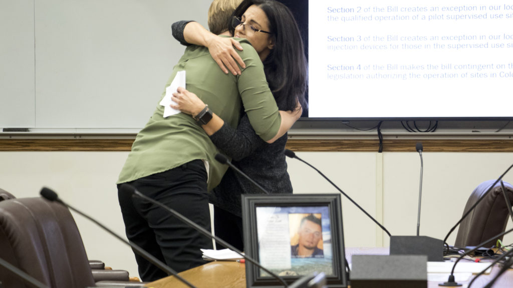 Joelle Fairchild hugs Lisa Raville, executive director of the Harm Reduction Action Center, during a Denver City Council meeting on safe injection sites. A picture of Fairchild's deceased son, Tony, is in the foreground. Nov. 7, 2018. (Kevin J. Beaty/Denverite)