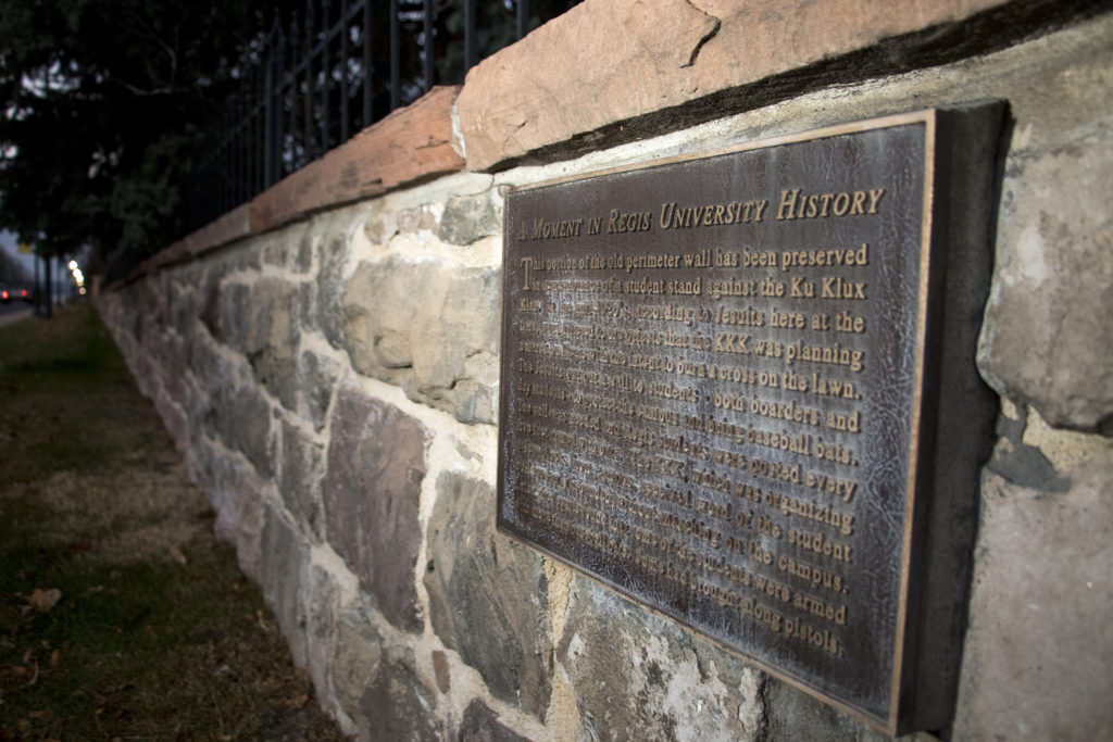 A century-old wall on Regis University's campus where, in the 1920s, students once repelled a group of Ku Klux Klansmen trying to burn a cross on the Jesuit school's lawn, Nov. 7, 2018. You can see a detail of the plaque here. (Kevin J. Beaty/Denverite)