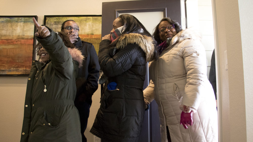 The Jackson family react as they see inside their new Commerce City home for the first time, Nov. 9, 2018. (Kevin J. Beaty/Denverite)