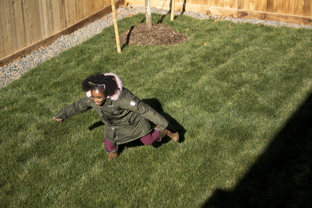 Amaya Jackson sprints around her family's new backyard in Commerce City, Nov. 9, 2018. (Kevin J. Beaty/Denverite)