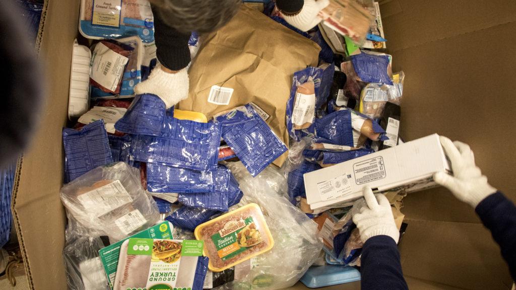Volunteers collect food for distribution inside Food Bank of the Rockies' warehouse in Aurora, Nov. 13, 2018. (Kevin J. Beaty/Denverite)