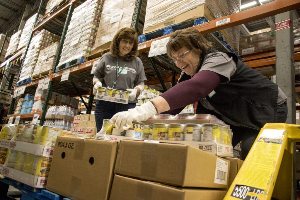 Andrea Koblischke (left) and Cathy Boller pack groceries for distribution at Food Bank of the Rockies' warehouse in Aurora, Nov. 13, 2018. (Kevin J. Beaty/Denverite)