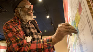 "A.D. Lewis sticks a pin in a map showing one of the places he's lived in his 60 years in Denver. ""Undesign the Redline,"" an interactive display at the Blair-Caldwell African American Research Library in Five Points, Nov, 15, 2018. (Kevin J. Beaty/Denverite)"