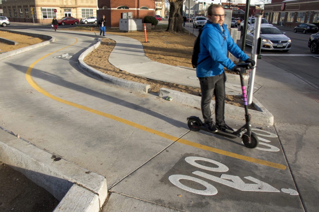 A man rides a Lyft scooter through a new bike crossing at Broadway, 21st and Champa Streets, Nov. 27, 2018. (Kevin J. Beaty/Denverite)