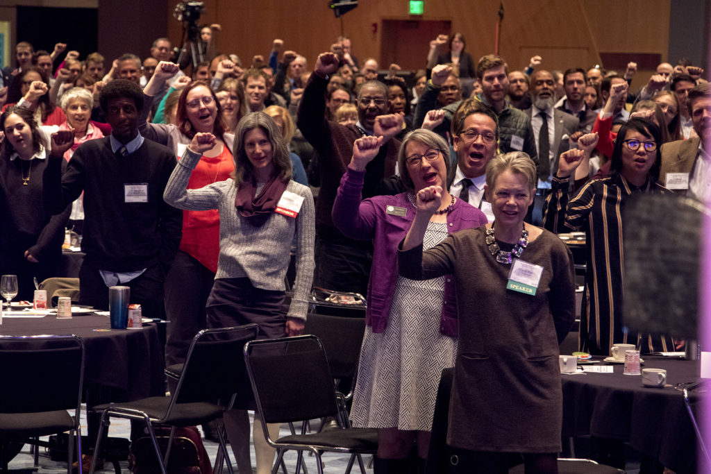 Denver officials (right) raise fists with the rest of the crowd as Mustafa Santiago Ali addresses the 2018 Sustainable Denver Summit at the Colorado Convention Center, Nov. 29, 2018. (Kevin J. Beaty/Denverite)