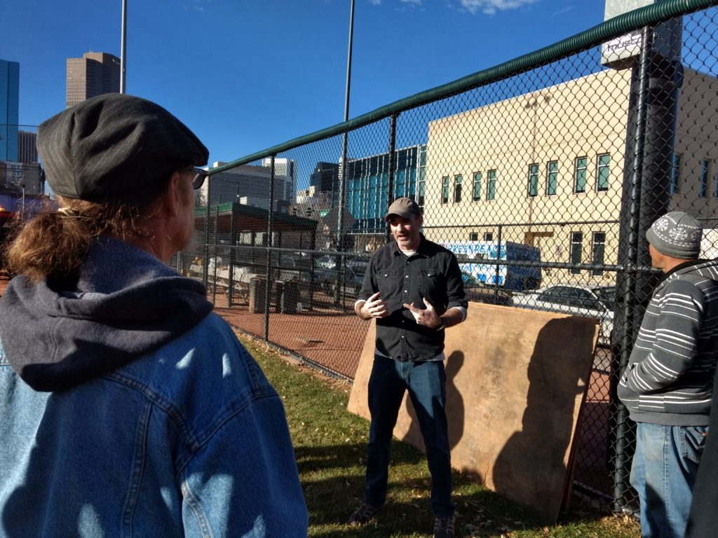 Chris Conner, director of Denver's Road Home, briefs workers helping him put up a holiday display meant to raise awareness about homelessness. (Donna Bryson/Denverite)