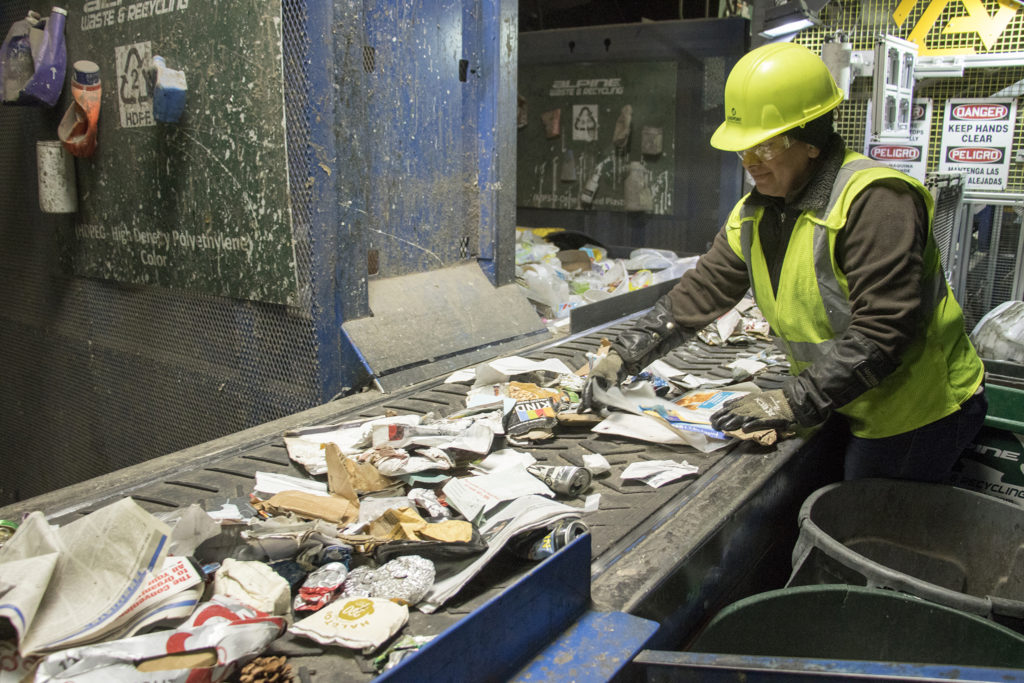 Yuderkarely Campps sorts recycled materials inside the Altogether Recycling center in Globeville, Dec. 3, 2018. (Kevin J. Beaty/Denverite)