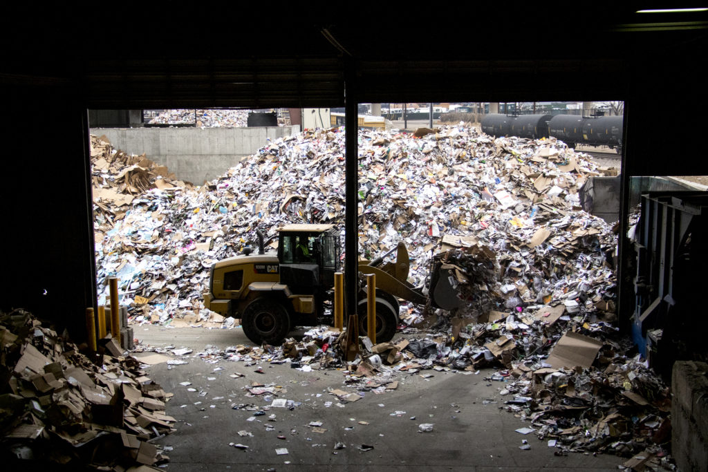 Unprocessed recycled material is loaded into the Altogether Recycling center. Globeville, Dec. 3, 2018. (Kevin J. Beaty/Denverite)