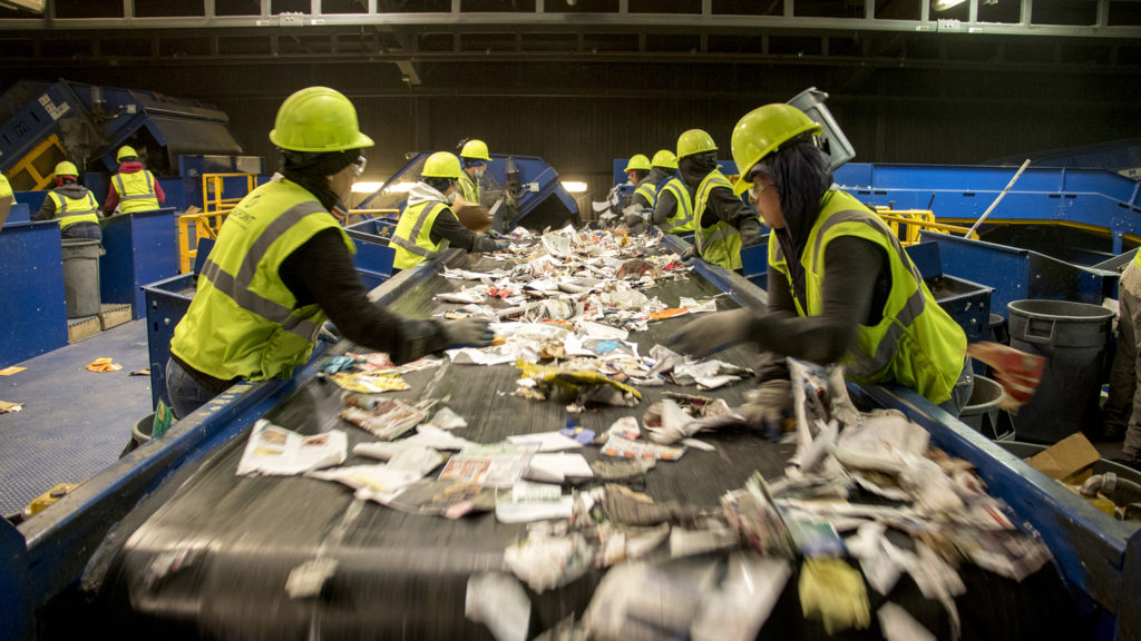 Workers pick through a stream of recycled materials inside the Altogether Recycling center in Globeville, Dec. 3, 2018. (Kevin J. Beaty/Denverite)