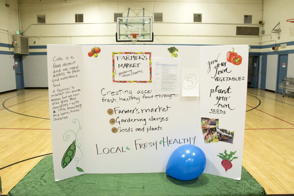 """A display for a proposal to bring a farmer's market to Cole. """"Cole Has A Soul"""" organizers meet at the St. Charles Recreation Center to unveil the winning ideas in their participatory budgeting project, Dec. 1, 2018. (Kevin J. Beaty/Denverite)"""
