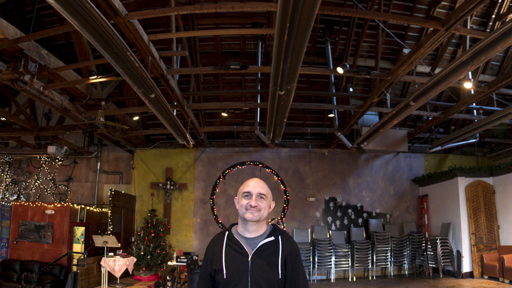 Jesse Heilmann, proprietor of Death and Glory Skate Shop, poses for a photo inside Scum of the Earth Church where his shop resides, Dec. 11, 2018. (Kevin J. Beaty/Denverite)