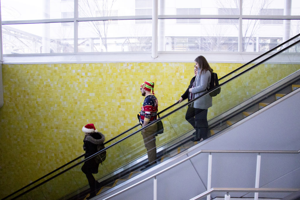 An elf rides an escalator at Chestnut Pavilion, the bus shelter at Union Station, Dec. 13, 2018. (Kevin J. Beaty/Denverite)
