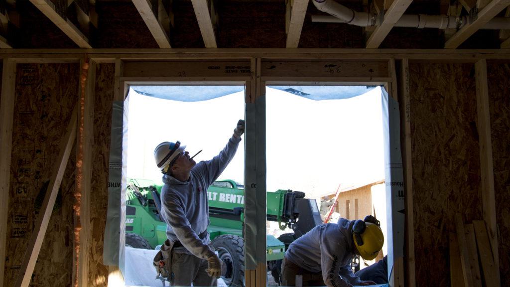 Chris Hartsen (left) and Samantha Filip work on a home in Habitat for Humanity's College View neighborhood site, Dec. 20, 2018. (Kevin J. Beaty/Denverite)