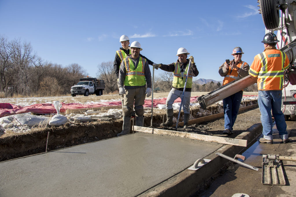 Workers preside over the first stretch of sidewalk funded by the 2017 GO bond in Bear Valley, Jan. 3, 2019. (Kevin J. Beaty/Denverite)
