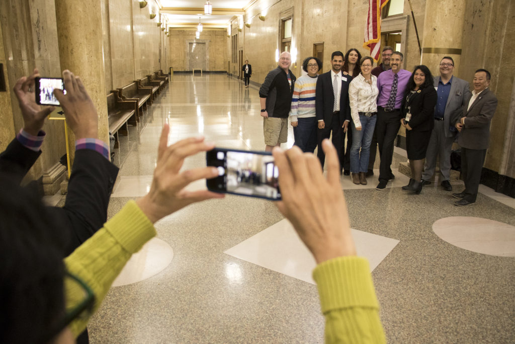 """Denver City Councilwoman Robin Kniech takes a photo with supporters after a bill banning """"conversion therapy"""" was passed, Jan. 7, 2018. (Kevin J. Beaty/Denverite)"""