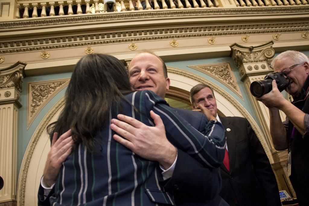 Governor Jared Polis hugs District 8 Rep. Leslie Herod before his first State of the State address, Jan. 10, 2019. (Kevin J. Beaty/Denverite)
