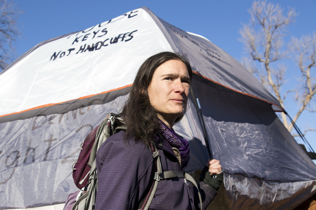 """Terese Howard holds a tent reading """"house keys not handcuffs"""" before the 2019 Martin Luther King Jr. Day Marade, Jan. 21, 2019. (Kevin J. Beaty/Denverite)"""