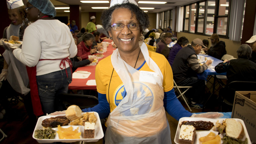 Diane Simpson, a volunteer with Sigma Gamma Rho Sorority Inc., poses for a portriat while on the job. Volunteers of America hosts their annual Martin Luther King Jr. Day dinner, Jan. 21, 2019. (Kevin J. Beaty/Denverite)