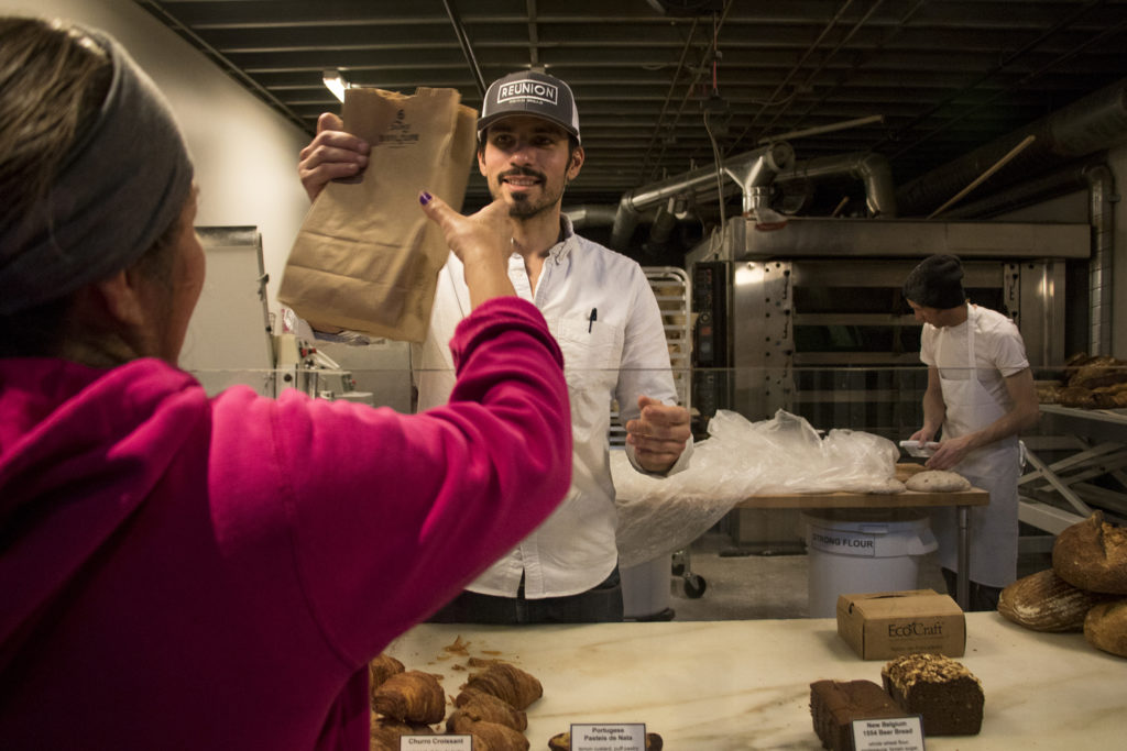 Reunion Bakery founder Ismael De Sousa helps a customer during his shop's soft opening at The Source in RiNo, Five Points, Jan. 22, 2019. (Kevin J. Beaty/Denverite)