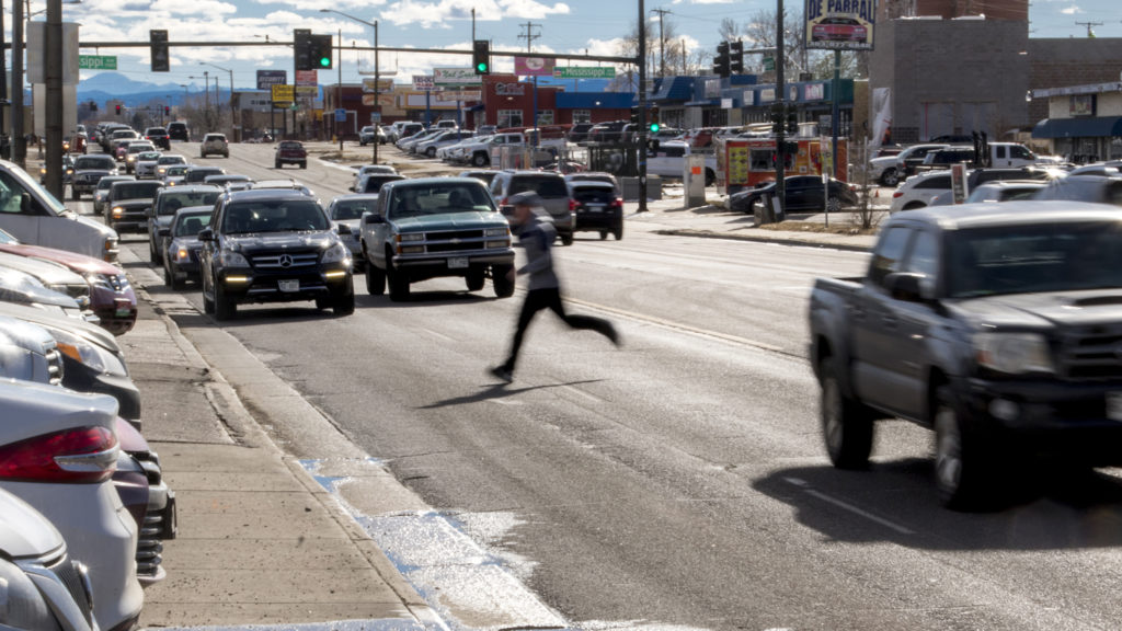 Christian Washington sprints between cars to cross Federal Boulevard, Jan. 26, 2019. (Kevin J. Beaty/Denverite)