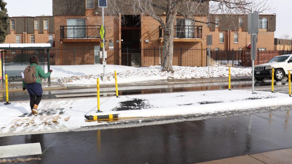 A woman crosses using Albrook Drive in Montbello using a pedestrian refuge. (David Sachs/Denverite)
