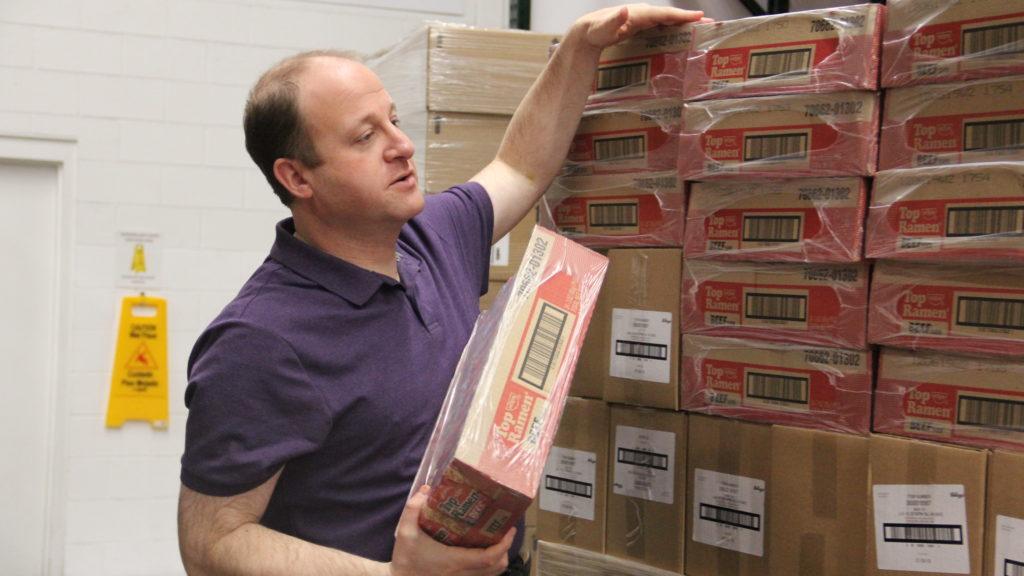 Gov. Jared Polis help stack instant ramen noodles at the Food Bank of the Rockies warehouse on Monday, Jan. 28, 2019, in Denver. (Esteban L. Hernandez/Denverite)