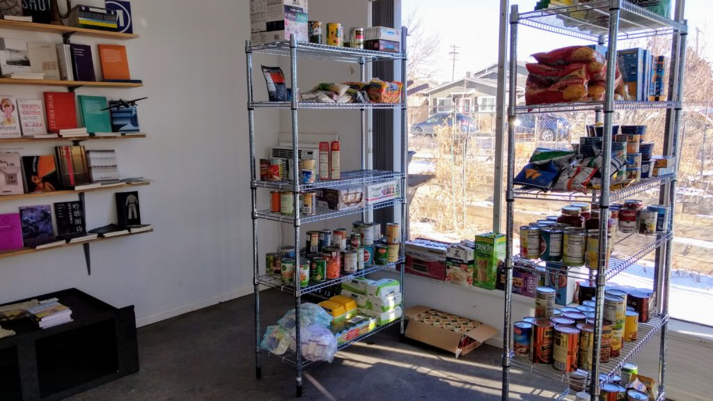 Books and food on the shelves at Counterpath, a publisher and exhibition space where the East Colfax Neighborhood Association has set up a food pantry. (Donna Bryson/Denverite)