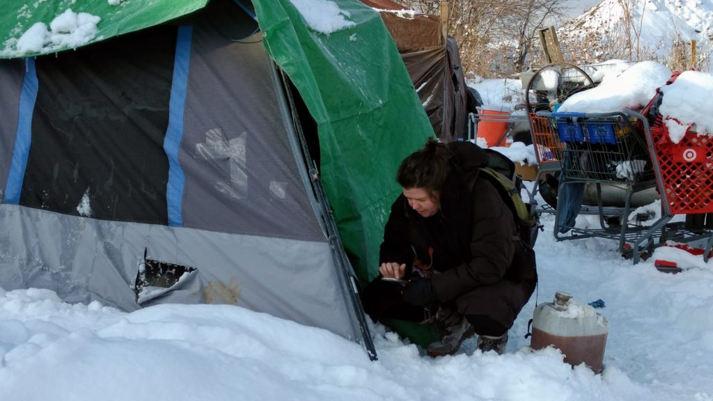 Megan Vizina, executive director of ACCESS Housing, conducts a Point-in-Time survey with a woman in a tent along Sand Creek. The woman was too cold to come out of her tent. (Donna Bryson/Denverite)