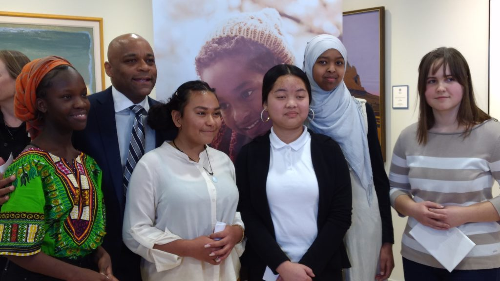 Mayor Michael B. Hancock in background with Place Bridge Academy students (from left to right) Grace Yose, Emmy Ramos, Salma Yusuf, Ro Win Na and Irina Vorobey at a Denver Human Services news conference. Place Bridge is one of three Denver Public Schools where DHS social workers are based.