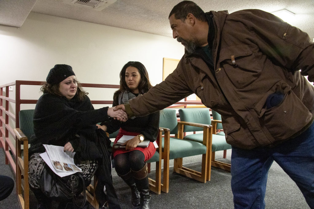 Mike Pacheco, a Globeville resident, apologizes to Luna Raine, who is in tears, on behalf of the neighborhood after comments made her leave the meeting in tears. Globeville residents meet with representatives from the city and the Beloved Community tiny home village, Feb. 7, 2019. (Kevin J. Beaty/Denverite)