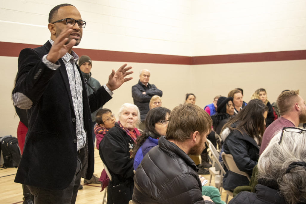 """City Councilman Albus Brooks delivers a """"come to Jesus"""" speech during the upheaval. Globeville residents meet with representatives from the city and the Beloved Community tiny home village, Feb. 7, 2019. (Kevin J. Beaty/Denverite)"""